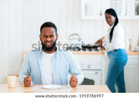 Portrait Of Starving Angry Black Man Waiting For Food At Table In Kitchen, Hungry African American Husband Sitting With Empty Plate And Looking At Camera, His Wife Cooking Lunch On Background Stock photo ©