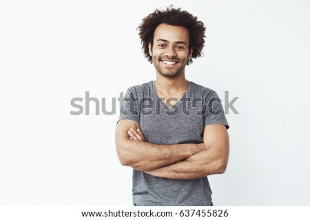 Portrait of stong and handsome african male student looking at camera smiling with crossed arms over white wall. Soon to be startup owner or salesman.