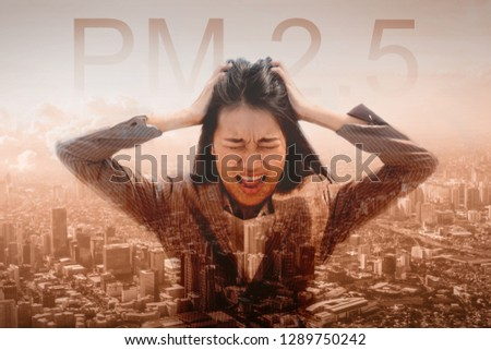 Portrait of stress Asian woman got headache with pm 2.5 concept background. Young Thai people over smog city suffering from headache desperate because pain, migraine from PM 2.5 dust and air pollution