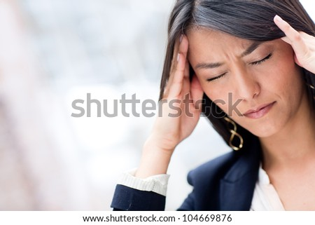 Portrait of stressed business woman with a headache