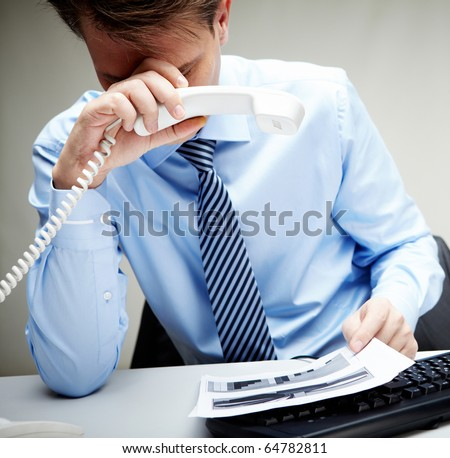 Portrait of stressed businessman with phone receiver in hand touching his head at workplace