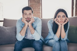 Portrait of stressed frustrated couple man woman sit divan have nothing to do on covid-19 quarantine feel bored wear denim jeans shirt in house indoors