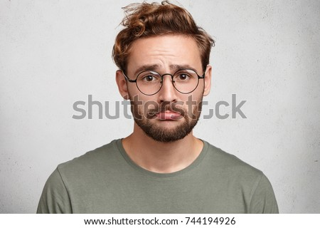 Portrait of stressed frustrated man curves lower lip being abused by someone, has temper tantrum, looks displeased into camera, isolated over white studio background. Depression, unhappiness concept #744194926