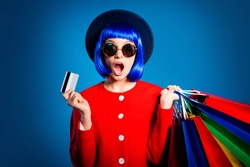 Portrait of stressed woman spent all earnings  savings salary holding plastic credit card and many colorful packets in hands with wide open mouth isolated on blue background
