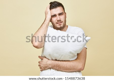 Portrait of stressed young brunette man suffering from headache keeping hand on his head and holding pillow can't fall asleep without sleeping pills, having depressed frustrated facial expression Foto stock ©