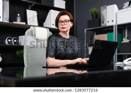Portrait of strict businesswoman with laptop in stylish office #1283977216