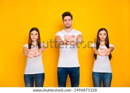 Portrait of strict mates crossing palms wearing white t-shirt denim jeans isolated over yellow background #1496875328