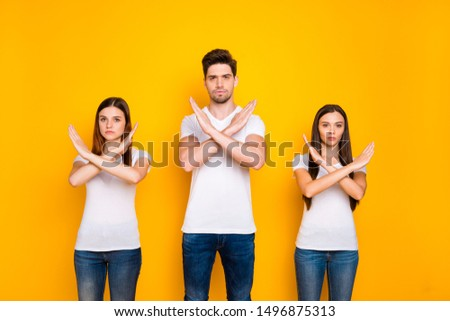 Portrait of strict youth crossing their hands wearing white t-shirt denim jeans isolated over yellow background #1496875313