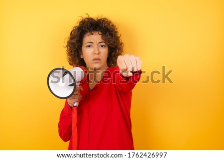 Portrait of strong and determined arab busineswoman in red shirt punching air with fist and looking confidently at camera, female struggle, fighting spirit. studio shot isolated on yellow background