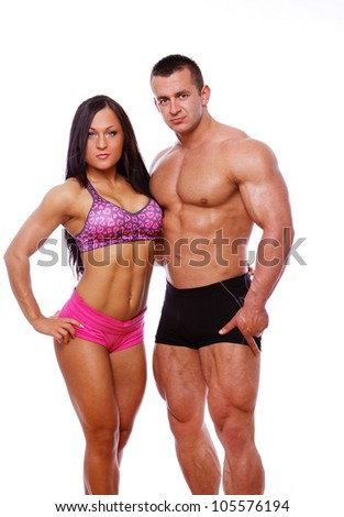 Portrait of strong couple posing in gym