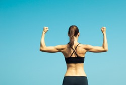 Portrait of strong female flexing.