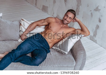 Portrait of strong healthy handsome athletic man. Fitness model posing and smiling while lying on the sofa. Fitness lifestyle concept.