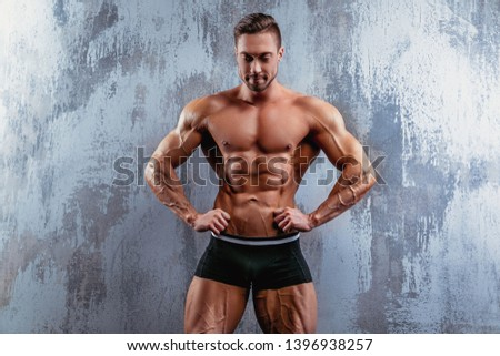 Portrait of strong healthy handsome athletic man. Fitness model posing near gray wall. Fitness lifestyle concept.