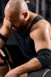 portrait of strong sporty man with bald head and thick beard, looking away, expressing power and strenth, dressed in black sportswear, sport bodybuilder concept