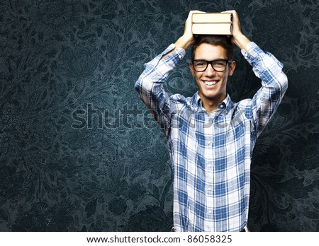 portrait of student with books on head against a grunge background