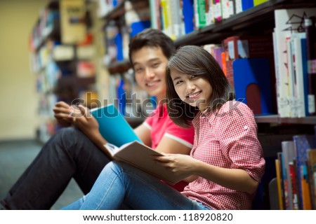 Portrait of students studying in library looking at the viewer with a cheerful smile