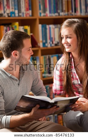 Portrait of students with a book looking at each other