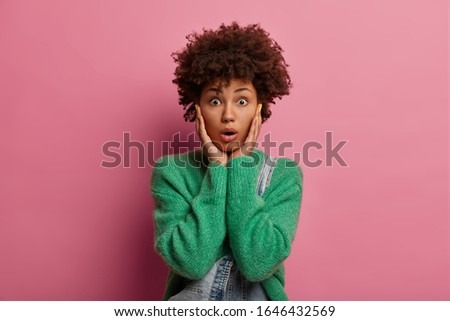 Portrait of stunned emotional curly woman grabs face, feels embarrassed and speechless, gasps from fear, hears unexpected gossip, wears green warm sweater, poses against rosy pastel background