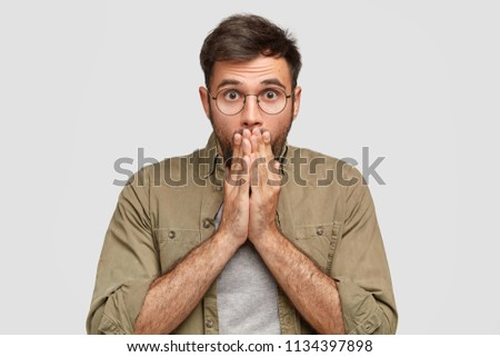 Portrait of stunned emotive bearded male covers mouth and stares at camera, hears awful news from friend, poses against white background. Emotional young Caucasian man stands indoor. Emotions #1134397898