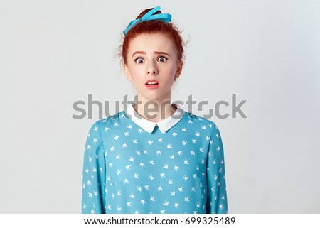 Portrait of stunned redhead young girl looking at the camera with shocked expression, mouth wide open, surprised with unexpected news. Isolated studio shot on gray background. #699325489