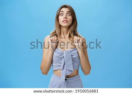 Portrait of stunned speechless and concerned young glamorous female pressing hands to chest popping eyes at camera standing in intense awkward and frightened pose being in stupor against blue wall Foto d'archivio ©