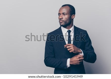 Portrait of stunning, trendy, attractive, dreamy, perfect man in black suit with tie fasten button on sleeve cuffs of white shirt, looking to the side, isolated on grey background #1029141949