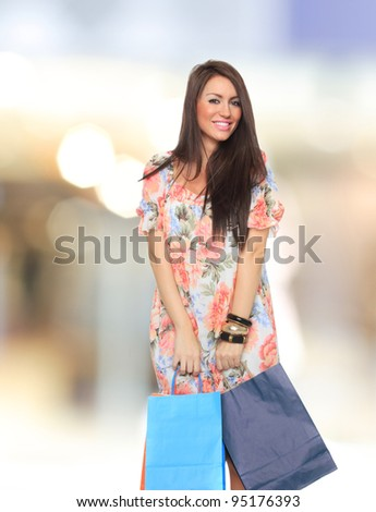 Portrait of stunning young woman carrying shopping bags
