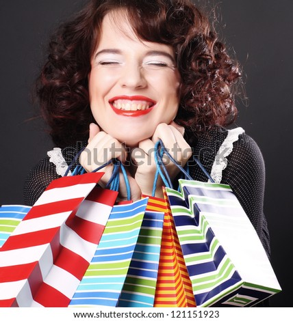 Portrait of stunning young woman carrying shopping bags against red background