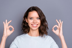 Portrait of style stylish lady with her curly brunette hair beaming hollywood smile she gives ok-sign on two hands stand isolated on gray wall