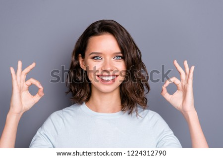 Portrait of style stylish lady with her curly brunette hair beaming hollywood smile she gives ok-sign on two hands stand isolated on gray wall #1224312790