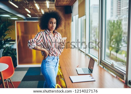 Portrait of stylish african american hipster girl chatting online in social networks on smartphone using 4G internet connection standing in coworking space.Dark skinned young woman blogging on phone