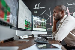 Portrait of stylish african businessman, trader sitting by desk in front of multiple monitors. He is getting angry while looking at current graphs. Stock trading, people concept. Side view