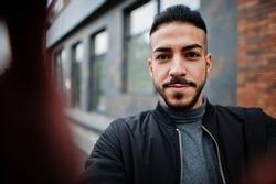Portrait of stylish arab beard man wear grey turtleneck and black jaket. Arabian model guy make selfie by camera.