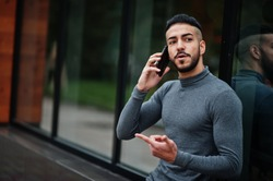 Portrait of stylish arab beard man wear grey turtleneck. Arabian model guy sit and speak by smartphone.