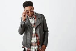 Portrait of stylish attractive young dark-skinned african male model with curly hair in black leather outwear taking off sunglasses with hand, looking in camera with cool and calm expression.
