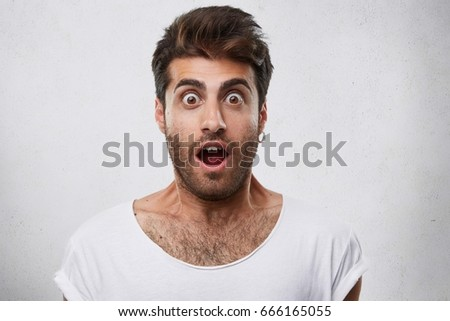 Portrait of stylish bearded guy having trendy hairstyle wearing earring and white T-shirt looking with his eyes popped out and opened mouth having shock and scared look. People and emotions concept #666165055