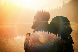 Portrait of stylish bearded man with glasses and tourism backpack.  Double exposure, view on  the beautiful mountain lake. Wide, sunset effect.