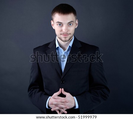 Portrait of stylish businessman looking at camera from darkness
