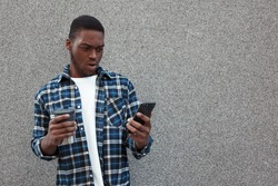 Portrait of stylish dark-skinned man posing outdoor against the wall shockingly looking at phone, holding thermo mug in his hand. Copy space. People, technology, lifestyle and OMG concept.