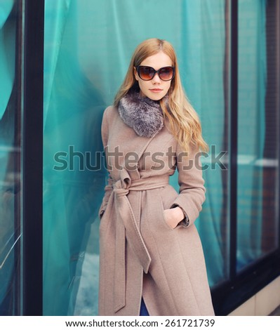 Portrait of stylish elegant woman in coat and sunglasses outdoors