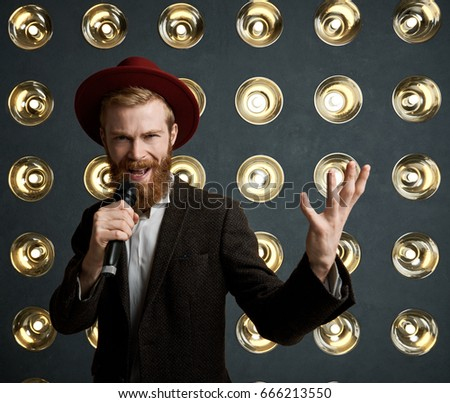 Portrait of stylish extravagant young bearded entertainer announcing next performer during concert, standing on stage against light decoration background, talking to audience using microphone.