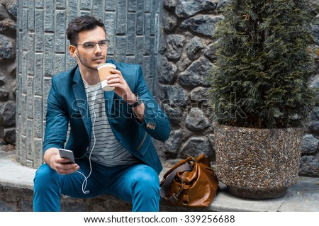 Portrait of stylish handsome young man with bristle standing outdoors. Man wearing jacket and watch. Man with glasses holding cup of coffee and using mobile phone