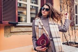 Portrait of stylish happy woman wearing coat scarf holding handbag outdoors. Spring fashion female retro accessories