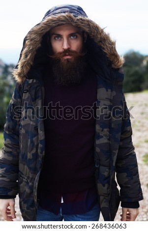 Portrait of stylish hipster model with red beard and beautiful blue eyes looking to the camera standing outdoors