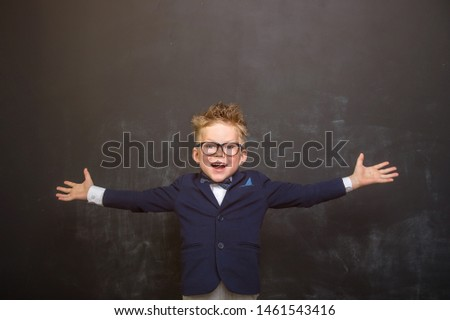 Portrait of stylish little boy in class blackboard with book. Little child in glasses has idea. Pupil in uniform. Success, bright idea, innovation technology, genius, businessman, dreams concept.