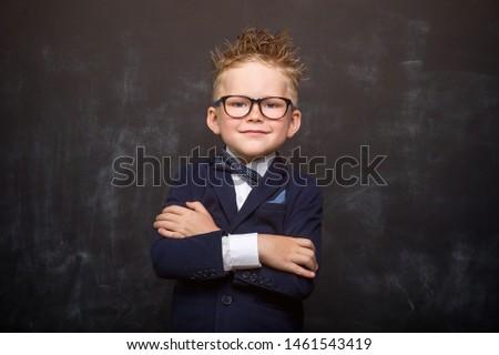 Portrait of stylish little boy in class blackboard with book. Little child in glasses has idea. Pupil in uniform. Success, bright idea, innovation technology, genius, businessman, dreams concept.