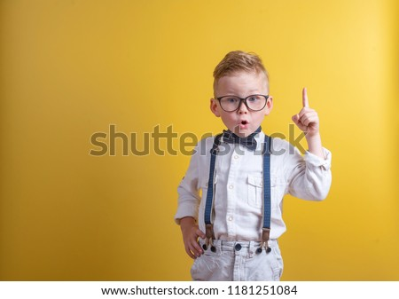 Portrait of stylish little boy with finger pointed up. Little child in glasses has idea. Kid isolated on yellow blackboard. Success, bright idea, creative ideas and innovation technology concept.