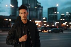 Portrait of stylish man on night city background pose to camera