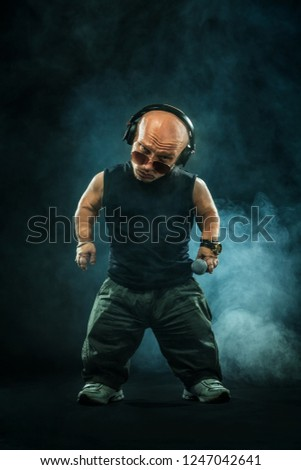 Portrait of stylish midget MC in with headphones and sunglasses posing with microphone.