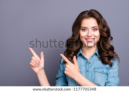 Portrait of stylish nice charming attractive cheerful magnificent adorable caucasian girl with wavy hair in casual denim shirt, pointing aside up, isolated over grey background
